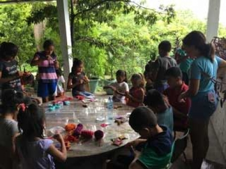 My daughter doing crafting with the children  (She is the one with the blue t-shirt with her back to us)